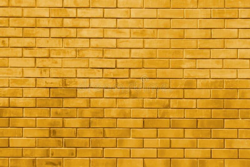 Gelbes Goldbacksteinmauerzusammenfassungs-Beschaffenheitshintergrund lizenzfreie stockfotografie