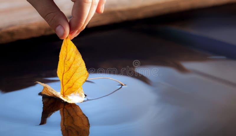 Gelbes Herbstblattschiff in den Kindern übergeben, Jungenspiel im Wasserteich lizenzfreie stockbilder