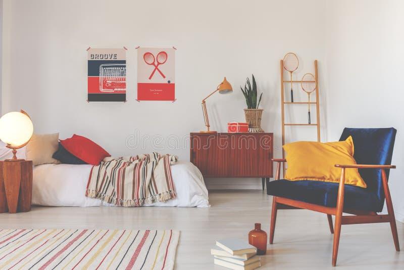 Gelbes Kissen auf blauem Weinleselehnsessel in stilvollem oldschool Schlafzimmer für Jugendlichen stockfotos