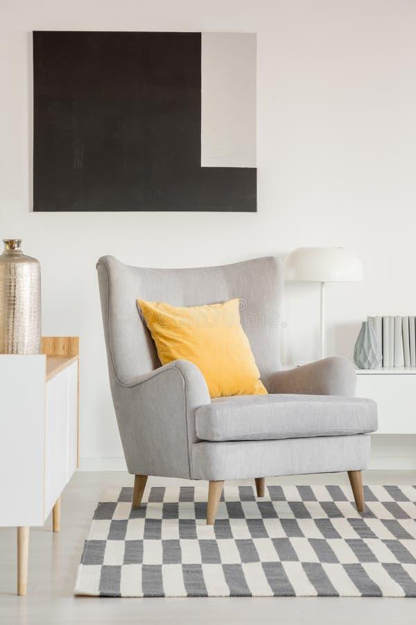 Gelbes Kissen auf grauem Lehnsessel im modernen Wohnzimmer Innen mit Schwarzweiss-Malerei stockfoto