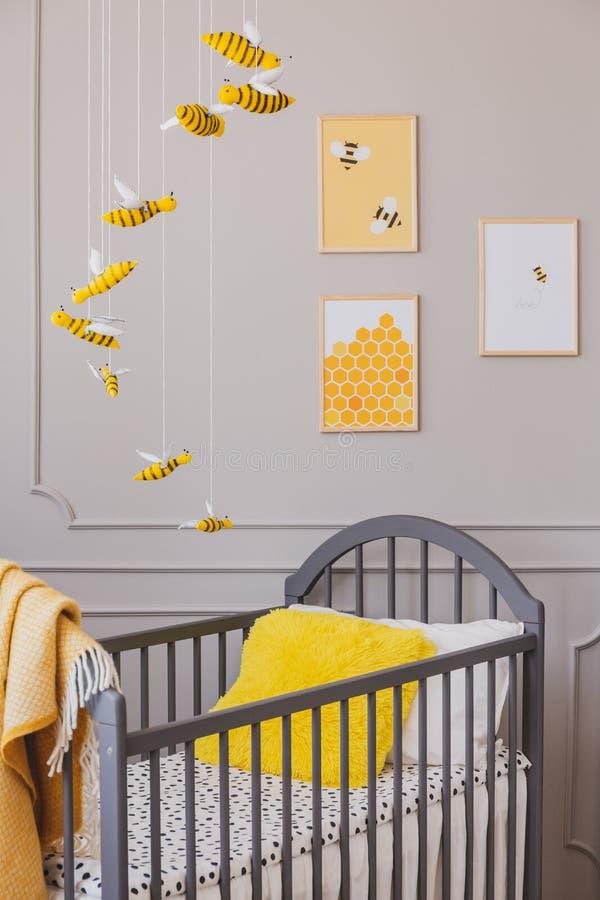 Gelbes Kissen in einer Krippe, in Bienenplakaten und in einer hängenden Dekoration in einem Kleinkindrauminnenraum Reales Foto stockfotografie