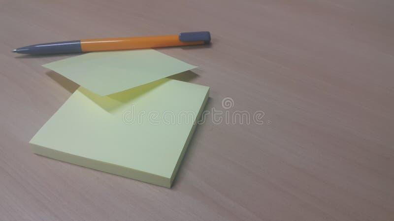 Gelbes klebriges Briefpapier mit dem Stift gesetzt auf einen Holztisch stockfoto