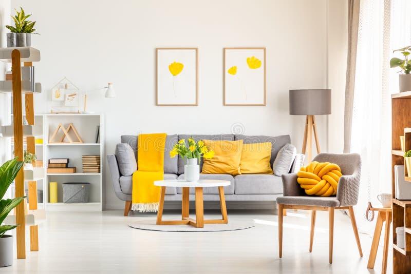 Gelbes Knotenkissen auf grauem Lehnsessel in modernem Wohnzimmer interi stockbild