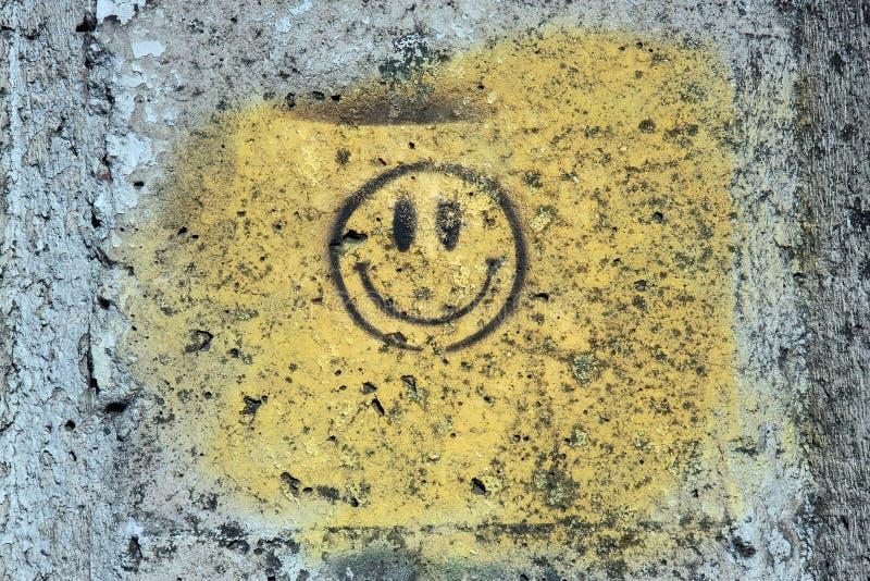 Gelbes Lächeln auf der grunge Wand lizenzfreies stockfoto