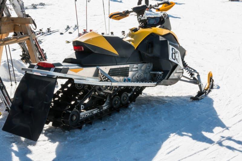 Gelbes laufendes Schneemobil fahrung am Wintertag stockfoto
