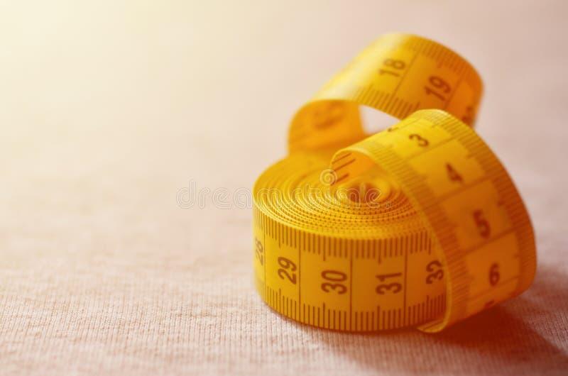 Gelbes messendes Band mit numerischen Indikatoren in Form von Zentimeter oder Zoll liegt auf einer grauen Maschenware Konzept Ind stockbild