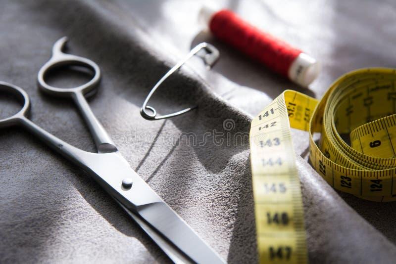 Gelbes messendes Band, Scheren und Spule des roten Threads auf grauem Gewebe stockbild