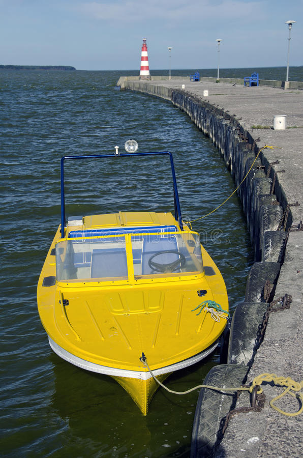 Gelbes Motorboot nahe Seedock und -leuchtturm stockbild