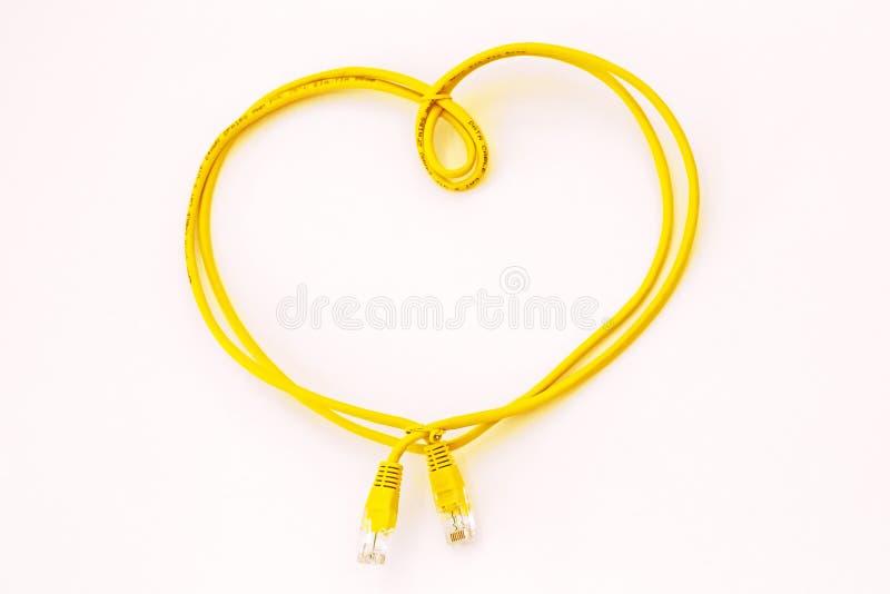Gelbes Netzkabel gefaltet in Form eines Herzens lokalisiert auf Wei? Safer Internet Day Welttelekommunikation und -informationen lizenzfreie stockfotografie