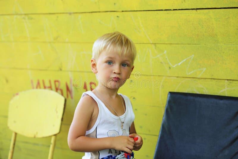 Gelbes Sommerhaus und ein kleiner Junge lizenzfreie stockbilder