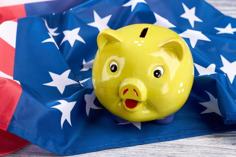 Gelbes Sparschwein auf amerikanischer Flagge stockfotos