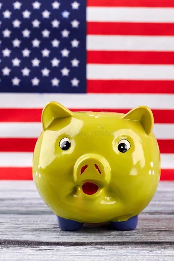 Gelbes Sparschwein auf Hintergrund der amerikanischen Flagge stockfotografie