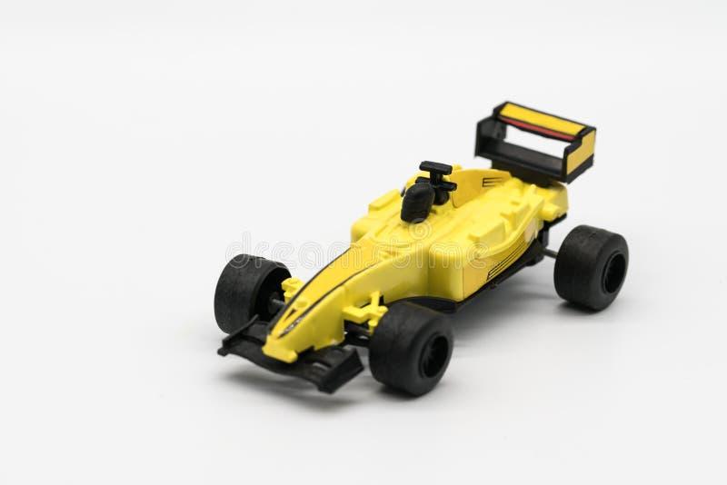 Gelbes Spielzeug als Formelauto lokalisiert auf Weiß stockfotografie