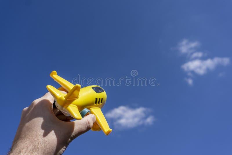 Gelbes Spielzeugflugzeugfliegen herein zum sch?nen blauen Himmel, negativer Raum, Konzept des Gehens an einem magischen Feiertag stockfotos