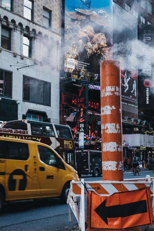 Gelbes Taxi fährt hinter den orange und weißen Stapel des Dampfdampfes in New York, USA stockfoto