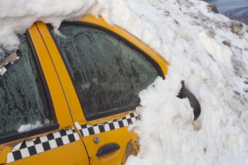 Gelbes Taxiauto bedeckt im Großen Stapel des Schnees stockfotos