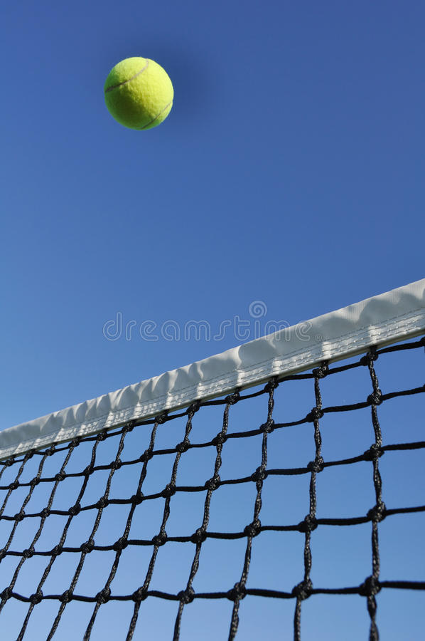 Gelbes Tennis-Kugel-Flugwesen über dem Netz lizenzfreie stockbilder
