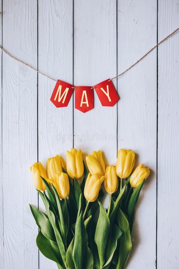 Gelbes Tulpenbündel auf ländlichem backgropund Tabelle der weißen hölzernen Scheune der Planken rustikalen Girlanden-Papierbeschr lizenzfreie stockbilder