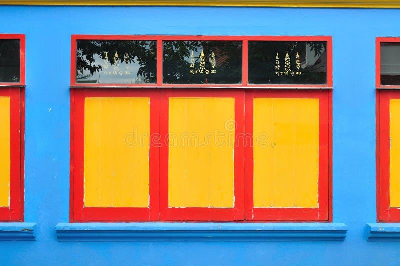 Gelbes und rotes Fenster auf einer blauen Wand. stockbild