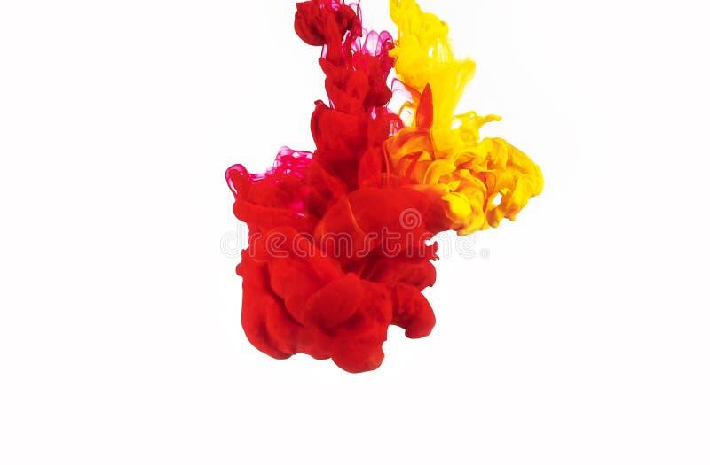 Gelbes und rotes Tintenspritzen lokalisiert auf weißem Hintergrund Tinte, die in Wasser wirbelt Bunte Tröpfchen der Tinte im Wass lizenzfreie stockbilder