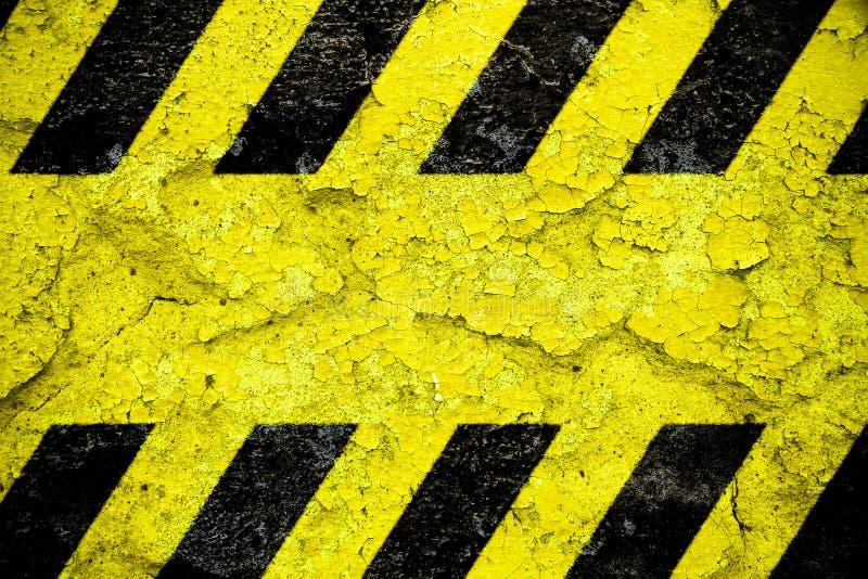 Gelbes und schwarzes Streifenmuster des warnenden Warnschildes mit gelbem Bereich über der konkreten Zementwandfassade, die gebr stockbilder