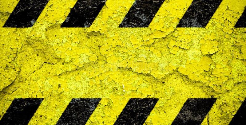 Gelbes und schwarzes Streifenmuster des warnenden Warnschildes mit gelbem Bereich ?ber der konkreten Zementwandfassade, die gebro lizenzfreies stockbild