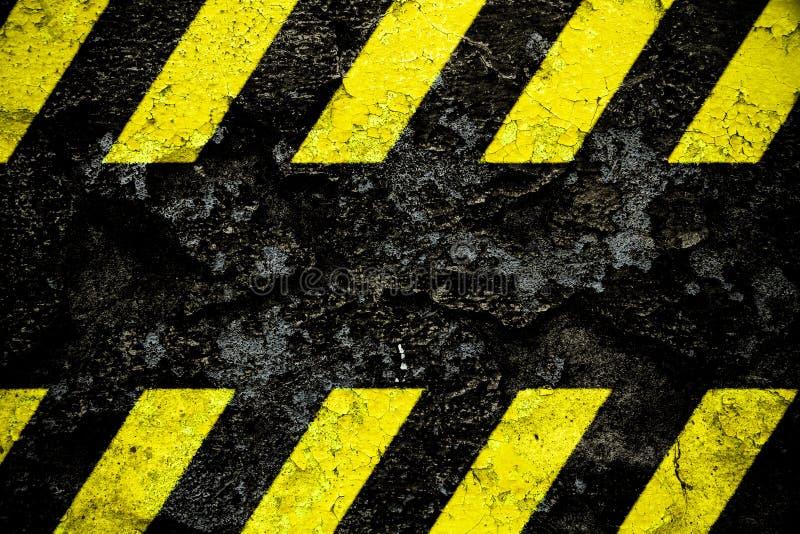 Gelbes und schwarzes Streifenmuster des warnenden Warnschildes mit schwarzem Bereich über der konkreten Zementwandfassade, die ge stockbild