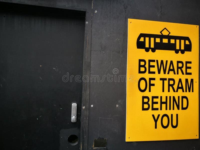 Gelbes Warnzeichen für Beware der Tram hinter Ihnen lizenzfreie stockfotografie