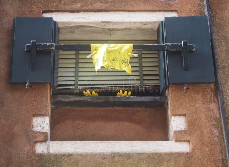 Gelbes Waschen herauf die Handschuhe und Stoff, die aus einem Fenster heraus hängen lizenzfreie stockfotografie