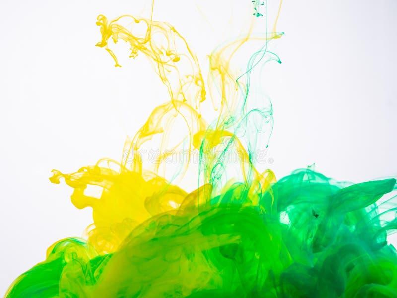 Gelbgrünes Acrylspritzen in der Flüssigkeit auf weißem Hintergrundabschluß oben Zwei Tintenfarben bei machen fotografiert lizenzfreie stockfotos