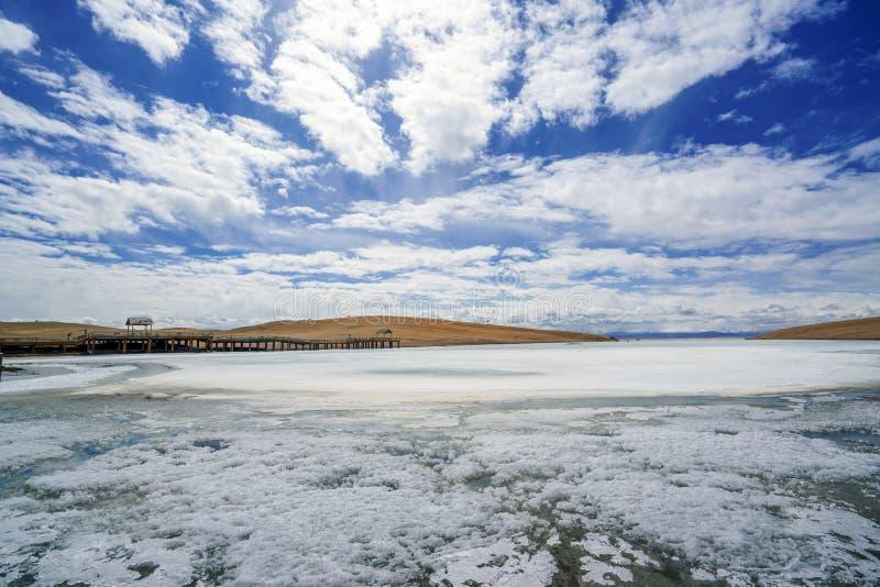 Gelbgras Fluss der weißen Wolken des blauen Himmels gefrorenes in Bayanbulak im Frühjahr lizenzfreies stockfoto