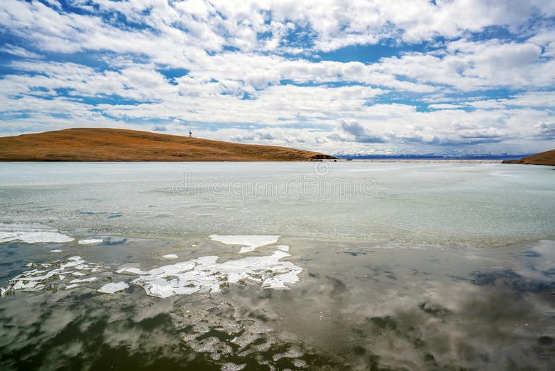 Gelbgras Fluss der weißen Wolken des blauen Himmels gefrorenes in Bayanbulak im Frühjahr stockfoto