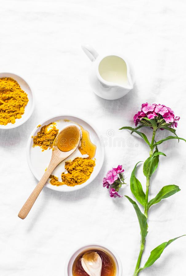 Gelbwurz, Honig, KokosmilchGesichtsmaske Selbst gemachte Bestandteilschönheitsprodukte auf einem hellen Hintergrund, Draufsicht r stockfotos