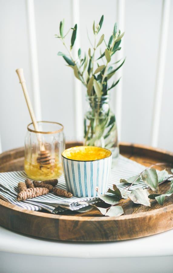 Gelbwurz Latte oder goldene Milch mit Honig auf hölzernem Behälter stockfotos