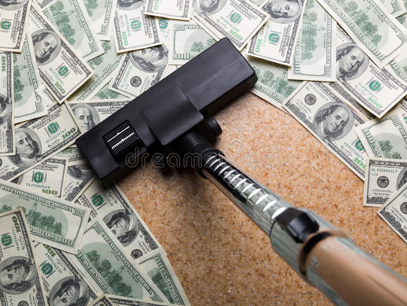 Geld auf dem Boden, der mit Staubsauger Staub saugt stockbild