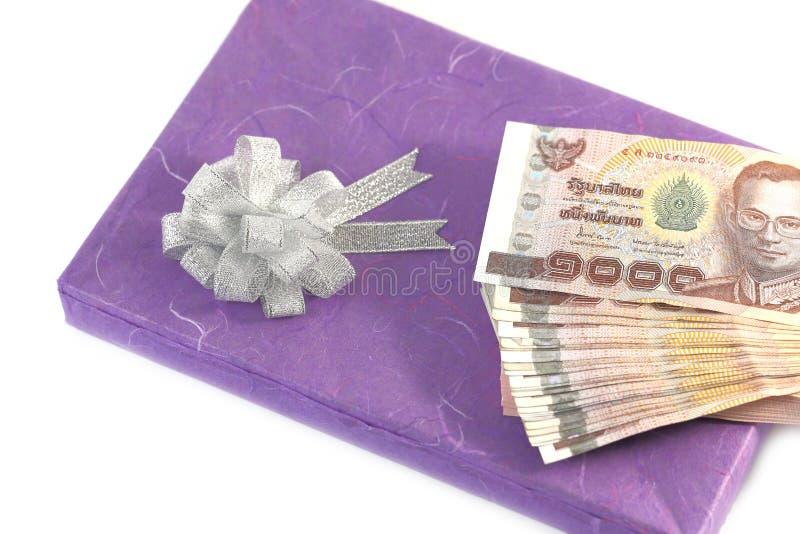Geld auf Geschenkboxpurpur lizenzfreies stockfoto