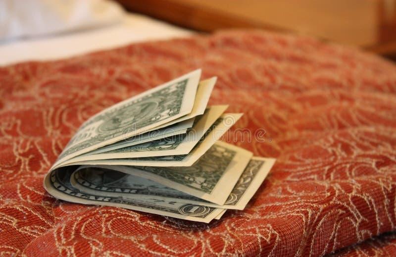 Geld auf Hotelbett lizenzfreies stockbild