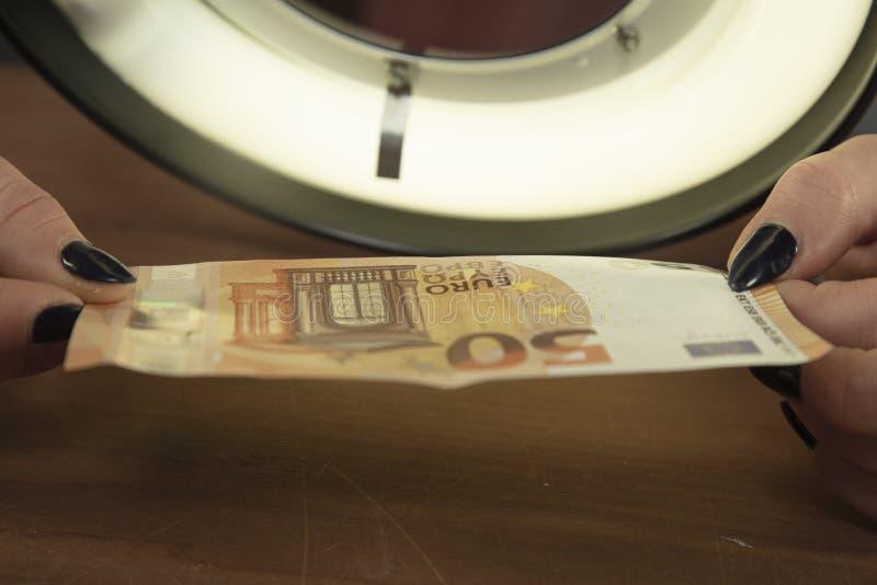 Geld authenticiteit wordt gecontroleerd die stock afbeeldingen