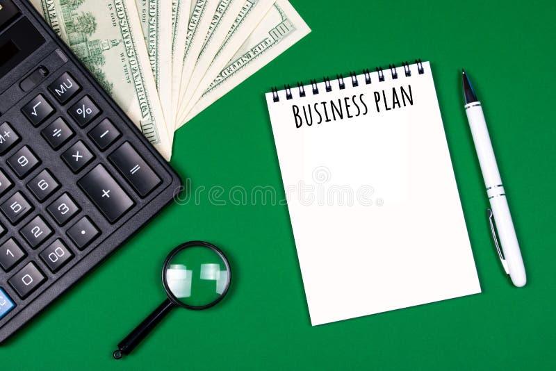 Geld, calculator en notitieboekje op groene achtergrond royalty-vrije stock afbeelding