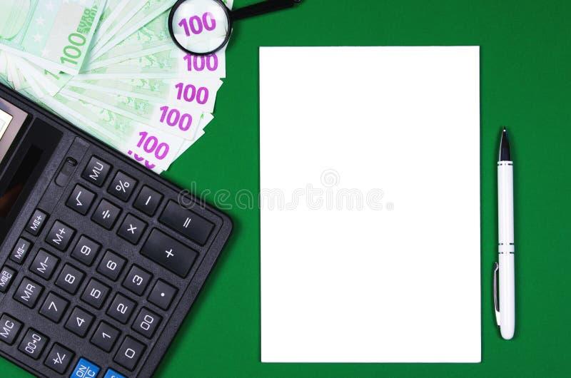 Geld, calculator en notitieboekje op groene achtergrond stock afbeeldingen