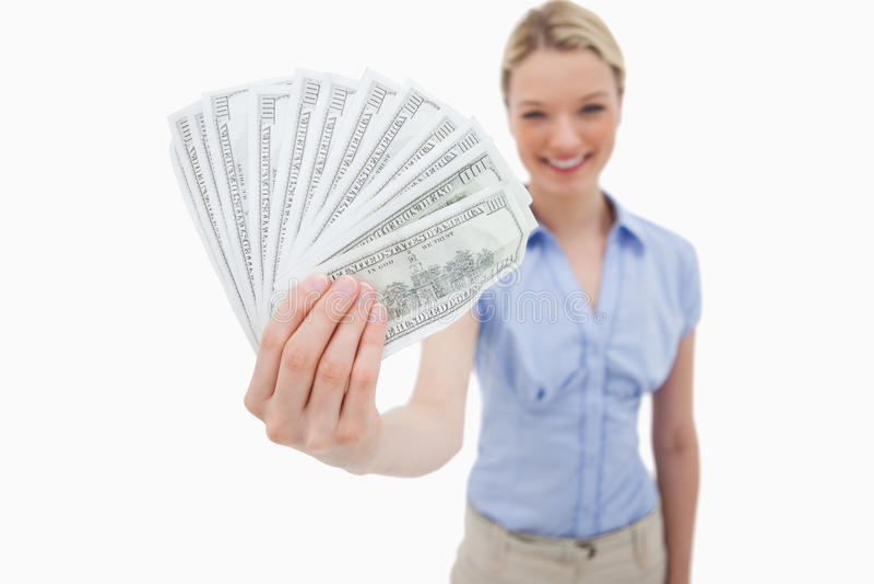 Geld, das von lächelnder Frau gehalten wird stockfoto