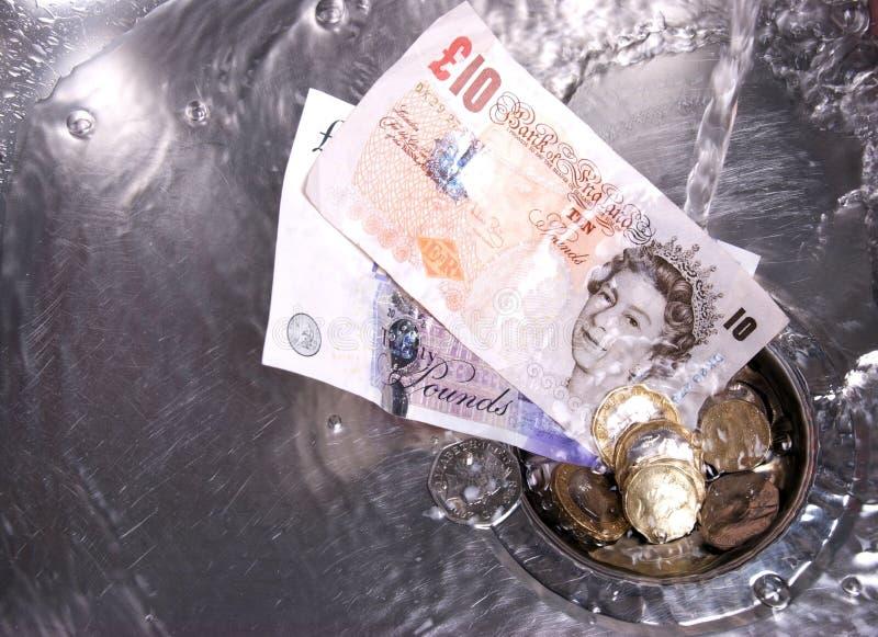 Geld dat onderaan het afvoerkanaal wordt gewassen stock foto