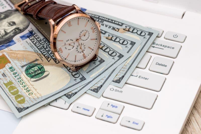 Geld, Dollaranmerkungen und Handuhr stockfoto
