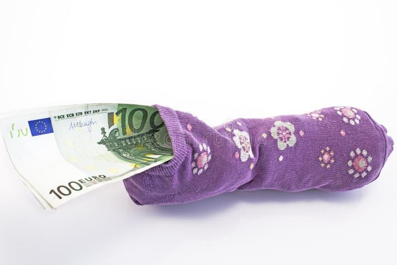 Geld in een sok op wit wordt geïsoleerd dat stock foto's