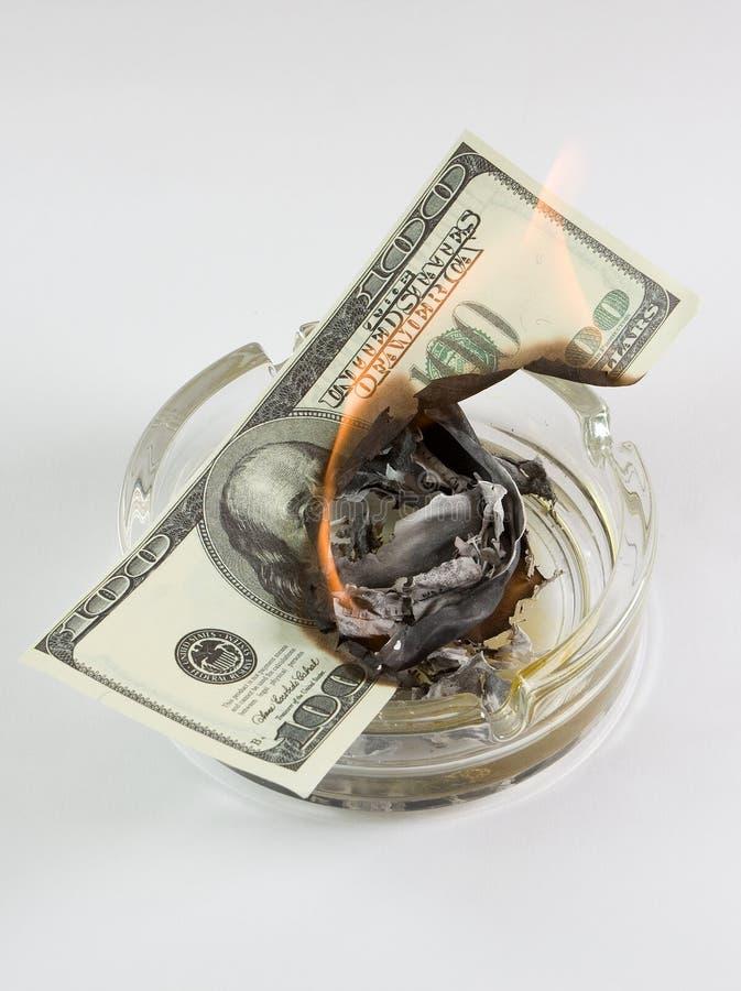 Geld in einem Aschenbecher brennt lizenzfreie stockfotos
