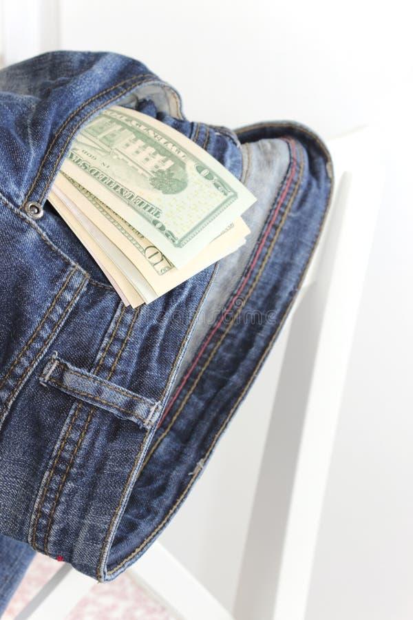 Geld in einer Tasche Jeans auf einer Rückseite des Stuhls lizenzfreie stockfotografie