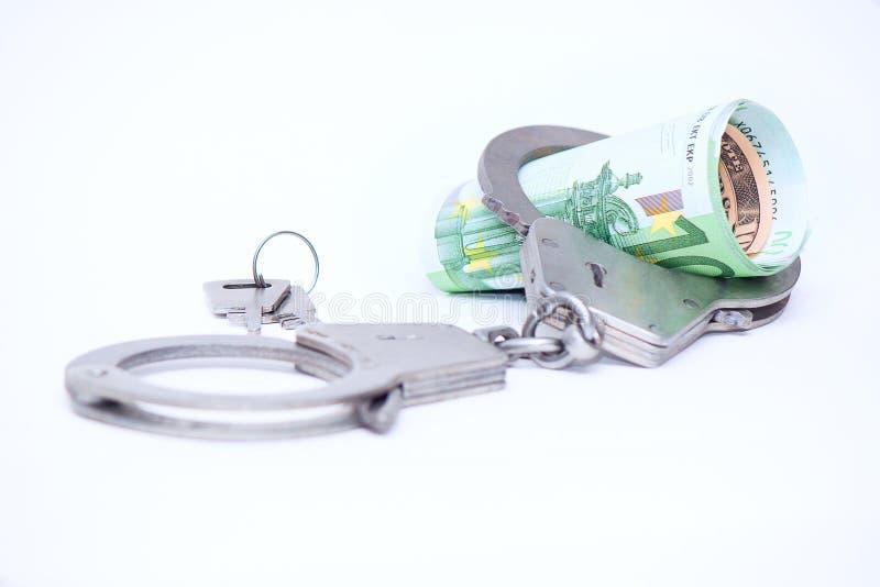 Geld en handcuffs Concept voor corruptie, fraude, geldwasserij, misdaad stock afbeelding
