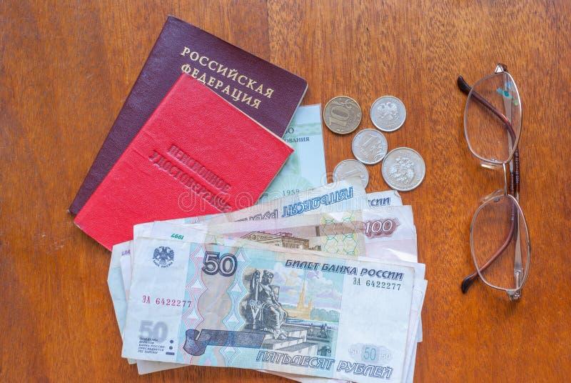 Geld, Gläser und Pensionszertifikat auf einer Holzoberfläche - russische Übersetzung: russische Pensionskasse Pensionär ` s Zerti lizenzfreie stockbilder