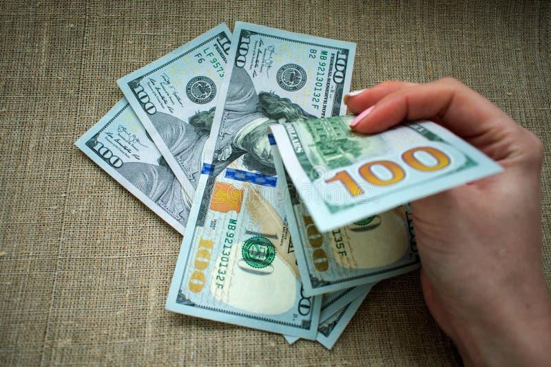 Geld ist in der Hand, eine Frau nimmt Geld stockbild