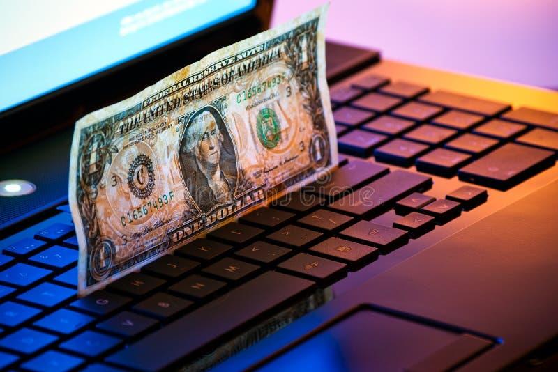 Geld op laptop stock afbeelding